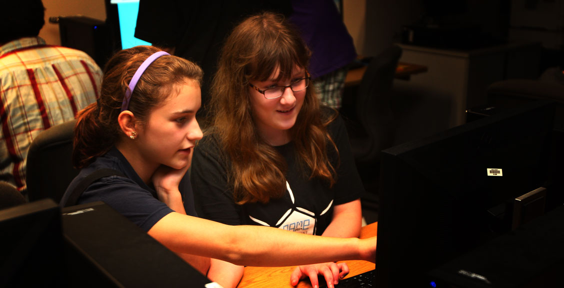 two smiling girls working together at a computer